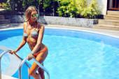 Aantrekkelijke vrouwelijke model in bikini bij het zwembad — Stockfoto