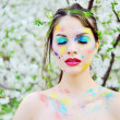 Beautiful woman with colored paint on face outdoor — Stock Photo #71462053