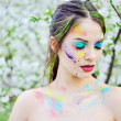 Beautiful woman with colored paint on face outdoor — Stock Photo #71462113
