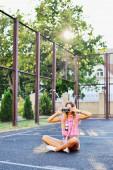 Stylish young woman using a camera to take photo outdoors — Stock Photo