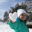 Lovely young woman showing snow heart — Stock Photo #63808055