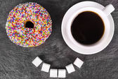 Humorous donut and coffee cup — Stock Photo