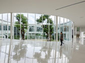 Glass wall in the building with people walking in motion blur — Stock Photo