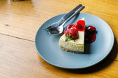 Strawberry Cheesecake on wooden table — Stockfoto