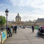 Paris, France - May 13, 2015: People visit Institut de France and the Pont des Arts in Paris — Stock Photo #75169449