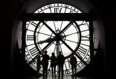 Paris, France - May 14, 2015: Silhouettes of unidentified tourists looking through the clock in the museum D'Orsay. — Stock Photo
