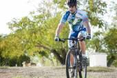 Ciclista en hacer una carrera en el campo de carreras de bicicleta de montaña — Foto de Stock