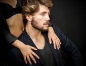 Handsome guy with a girl hands resting on his shoulder — Stock fotografie