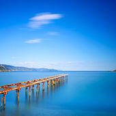 木码头仍然在蓝色的海洋的湖面上。长时间曝光 — 图库照片