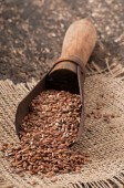 Old measuring scoop with flax seeds — Stock Photo