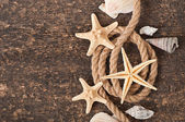 Starfish and shells on old wooden background — Stok fotoğraf