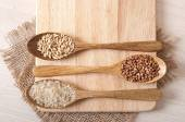 Wooden spoons and buckwheat, rice and oats — Stock Photo