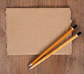 Paper and pencil on a wooden background — Stock Photo