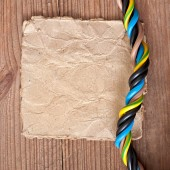Paper and electrical cable on the old wooden background — Stock Photo