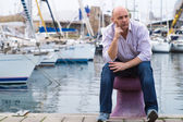 Businessman sitting by expensive sailing boats and yachts in a c — Stock Photo