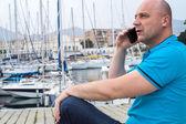Businessman talking on the phone close to the luxurious harbor — Fotografia Stock