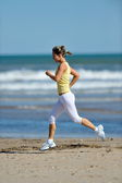 Young woman jogging on the beach in summer day — Stock Photo