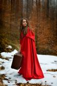 Beautiful woman with red cloak and suitcase alone in the woods — Photo
