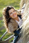 Beautiful young woman relaxing under a hay stack in autumn — Stock Photo