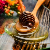 Golden honey on plate and colorful flowers — Stock Photo