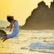 Young woman jumping on the beach in summer evening — Stock Photo #71942063