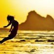 Young woman jumping on the beach in summer evening — Stock Photo #71942007