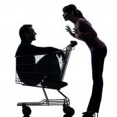 Couple woman  with man sitting in shopping cart silhouette — Stock Photo
