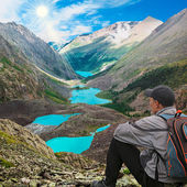 Hiker with backpack sitting on top of the mountain — Stock Photo