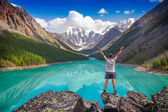 Young hiker standing with raised hands near the beautiful mountain lake and enjoying valley view — Stock Photo