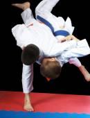 Beautiful high throw are doing  sportsmen in judogi — Stock Photo