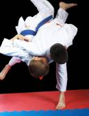 Very high throw in performing sportsman with orange belt — Stock Photo