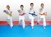 Punch arm in the performance of four athletes in karategi — Stock Photo