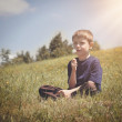 Boy Making Dandelion Wish on a Green Hill — Stock Photo #73134237