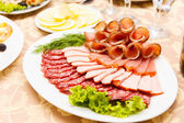 Dish with sliced meat products — Stock Photo