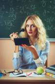 Beautiful young teacher making-up — Stock Photo