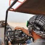 Men riding buggy car in desert — Stock Photo #75316861