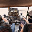 Young couple riding buggy car in desert — Stock Photo #75316547