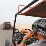 Men riding buggy car in desert — Stock Photo #75316903
