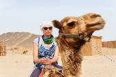 Young caucasian woman tourist riding on camel — Stock Photo