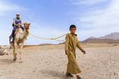 Arab boy rolls tourists on a camel. — Stock Photo