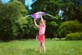 Niña juega con color cometa en el Parque. — Foto de Stock