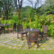 Wooden dining tables set in garden setting — Stock Photo #59222355
