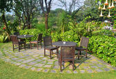 Wooden dining tables set in garden setting — Stock Photo