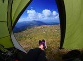Frau in zelt mit blick auf berg und himmel — Stockfoto