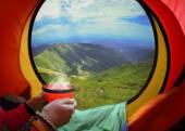 Woman lying in a tent with coffee ,view of mountains and sky — Stock Photo