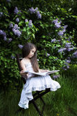 Cute little girl, dressed in a white dress,  sitting in the garden in the park and reading a book. Blooming lilacs in the background — Stock Photo