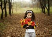 Cute girl with dark curly hair sitting in the autumn forest with a bouquet of rowanberry — Stock Photo