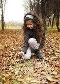 Little cute girl with dark curly hair sitting in the autumn forest with a  bunch of leaves — Stock Photo