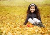 Little cute girl with dark curly hair sitting in the autumn forest with a bouquet of leaves — Stock Photo