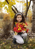 Little cute girl with dark curly hair sitting in the autumn forest with a bouquet of rowanberry — Stock Photo